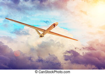 Unmanned military aircraft drone flies the at sunset clouds sky.