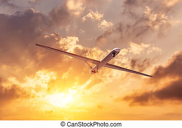 Unmanned military drone flies the at sunset clouds sky.