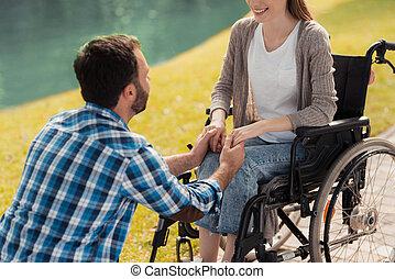 uno, donna, è, seduta, in, uno, wheelchair., uno, uomo, è, seduta, accanto a, lei, e, presa a terra, lei, hands.
