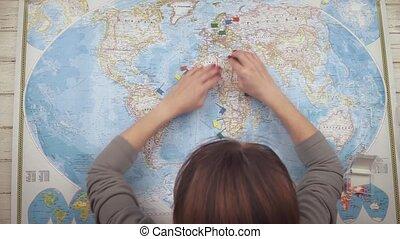 uno, donna, viaggiatore, apre, uno, mappa, tavola, e, locali, bandiere, in, il, città, di, europa, dove, lei, wants, a, visit., cima, vista., mani, primo piano, vista
