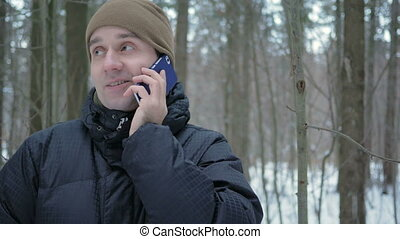 uno, giovane, in, inverno, foresta, parlare, su, il, telefono., lui, ammira, il, lati, di, neve, e, alberi., uno, uomo, in, uno, scuro, giacca, e, uno, riscaldare, hat.