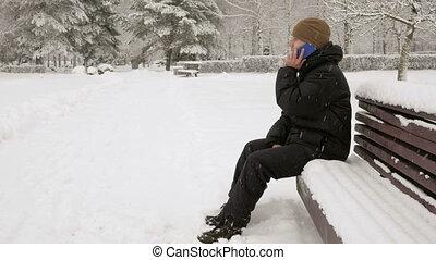 uno, giovane, in, inverno, parco, parlare, su, il, telefono., lui, ammira, il, lati, di, neve, e, alberi., uno, uomo, in, uno, scuro, giacca, e, uno, riscaldare, hat.