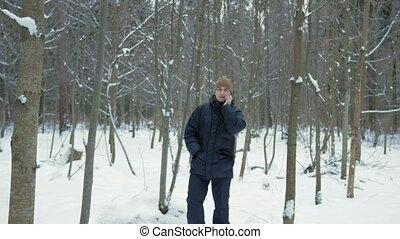 uno, giovane, va, su, uno, inverno, foresta, e, parlare, su, il, telefono., lui, blocca il funzionamento, e, fini, il, conversation., uno, uomo, in, uno, scuro, giacca, e, uno, riscaldare, hat.