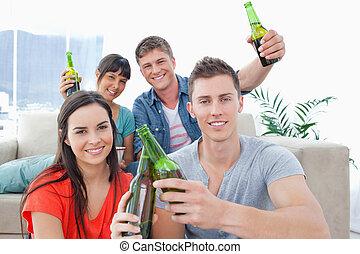 uno, gruppo amici, festeggiare, vicino, clinking, bottiglie, insieme