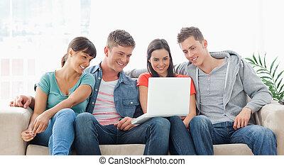 uno, gruppo amici, sedere, insieme, divano, osservare, il, laptop, mentre, sorridente