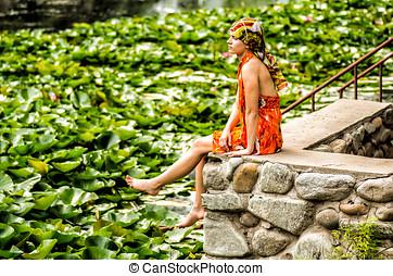 uno, ragazza, è, seduta, su, uno, banchina, guardando, il, lago, con, loto