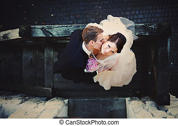 uno, sguardo, dal di sopra, su, il, sposo, baciare, sposa, collo, mentre, essi, stare in piedi, su, il, legno, staira, esterno