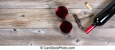 Unopen bottle of red wine with old corkscrew and full drinking glasses on rustic wooden boards