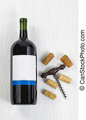 Unopened large bottle of red wine with an antique corkscrew and