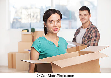 Unpacking at their new house. Beautiful young woman holding an opened cardboard box and smiling at camera while cheerful man standing on background