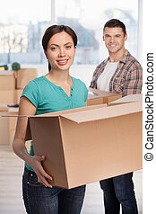 Unpacking boxes. Attractive young woman holding an opened cardboard box and smiling at camera while cheerful man standing on background