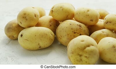 Unpeeled clean potatoes in closeup - Closeup shot of pile of...