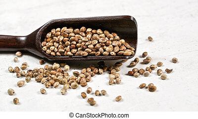 Unpeeled hemp - Cannabis sativa - in small dark wooden spoon on white stone board desk