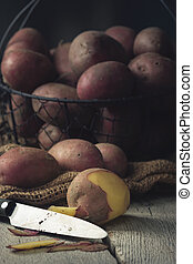 unpeeled Potatoes in a Basket with Knife