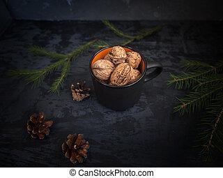 Unpeeled walnuts in a black ceramic mug closeup