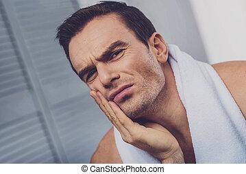 Sad unhappy man holding his cheek