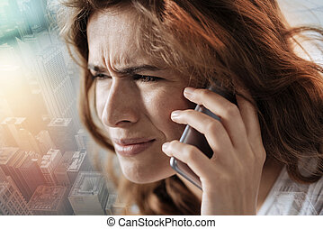 Close up of a depressed woman talking on phone