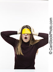 Unpleased Exclaiming Caucasian Woman in Burgundy Turtleneck Sweater With Yellow Sticky Note on Her Forehead. Against White Background.