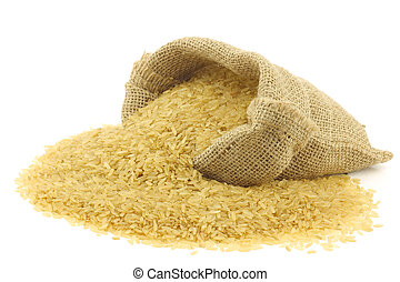 unpolished rice (whole grain) in a burlap bag on a white ...