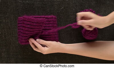 Unravelling the woolen scarf - Female hands unravelling the...
