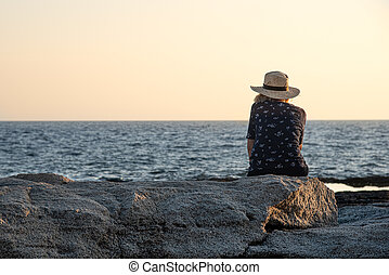 Unrecognised woman sitting on a rock enjoying the sea at ...