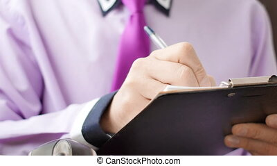 Unrecognizabel young businessman writing in clipboard