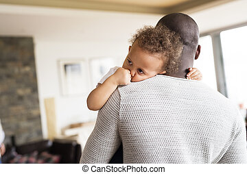 Unrecognizable afro-american father holding his little daughter