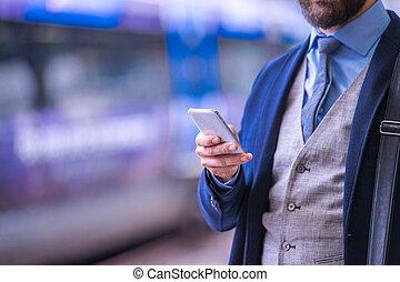 unrecognizable, attente, train, smartphone, homme affaires