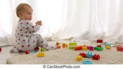 Unrecognizable baby playing with toy bricks - Back view of...