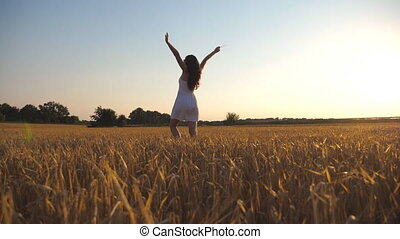 Unrecognizable beautiful girl walking along wheat field and raising her hands. Young woman going at the meadow and enjoying freedom. Summer leisure at nature concept. Side view Close up Slow motion