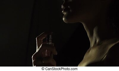 Unrecognizable beautiful woman sprays her perfume on her neck, slow motion video