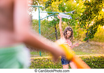 Unrecognizable boy splashing girl with water gun, sunny summer