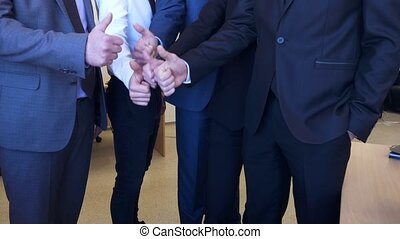 Unrecognizable business people showing their thumbs up.