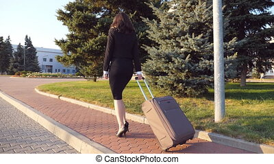 Unrecognizable business woman with suitcase walks to the airport to go on business trip. Lady in high heels shoes stepping with her luggage along street. Travel concept. Back view Slow motion Close up