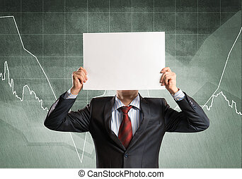 Businessman and graphs at background hiding his face behind paper
