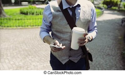 Unrecognizable businessman in park with coffee, making phone call.