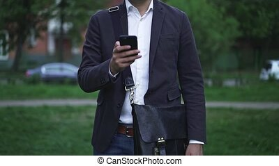 Unrecognizable businessman texting on his smartphone, blurred summer city