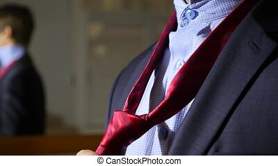unrecognizable businessman tightens his tie. 4k, slow motion. details, close-up