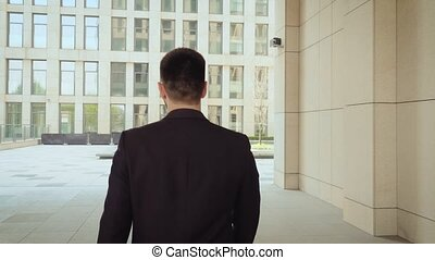 Unrecognizable businessman walking around city, successful and self-confident man on the background of a modern building. Back view
