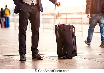 Unrecognizable businessman with luggage waiting at the...