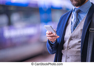 Unrecognizable businessman with smartphone, waiting at the train