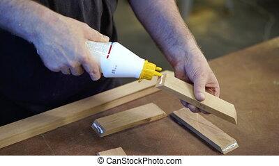 Unrecognizable carpenter applies glue to wooden parts. ...