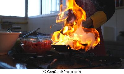 Unrecognizable chef cooking tasty flambe style dish on pan...
