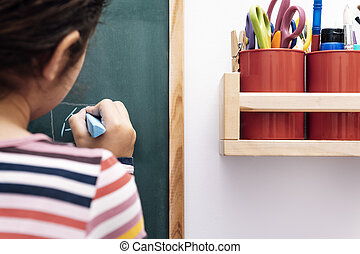 unrecognizable child drawing on a blackboard