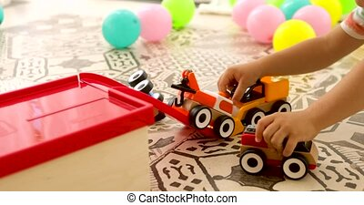 Unrecognizable child playing toy cars on floor - Crop kid...