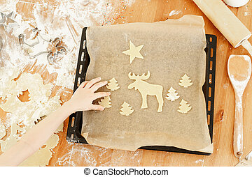 Unrecognizable child puts ready hand made cookies on baking tray, helps mother with preparation for Christmas. Butter Christmas cookies. Tasty ginger bread.