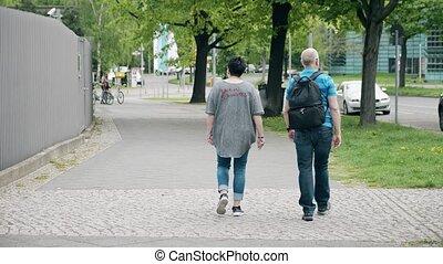 Unrecognizable couple walk along the street in Berlin