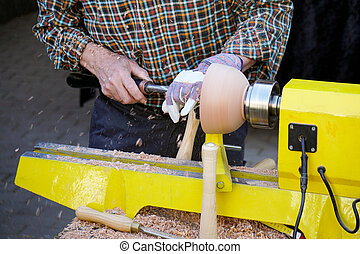 unrecognizable craftsman turning wood with lathe