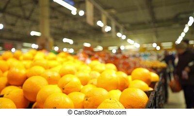 Unrecognizable customers in supermarket choose oranges