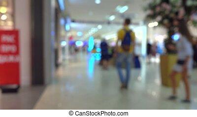 Unrecognizable customers walking in modern shopping center. 4K bokeh video